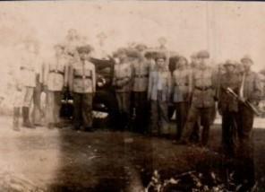 Grupo de soldados ao lado de transporte de tropas.