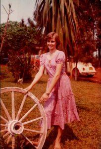 Terezinha com roda de carroça, relíquia do passado.